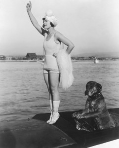 1916: American actor Gloria Swanson (1899 - 1983) stands on tiptoes on the prow of a motorboat while Teddy the dog sits with his paws on the steering wheel in a still from director Clarence G Badger's film 'Teddy at the Throttle'.